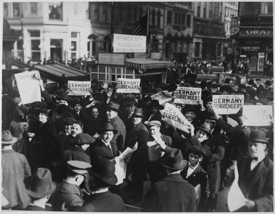 men holding signs that say 'Germany surrenders'