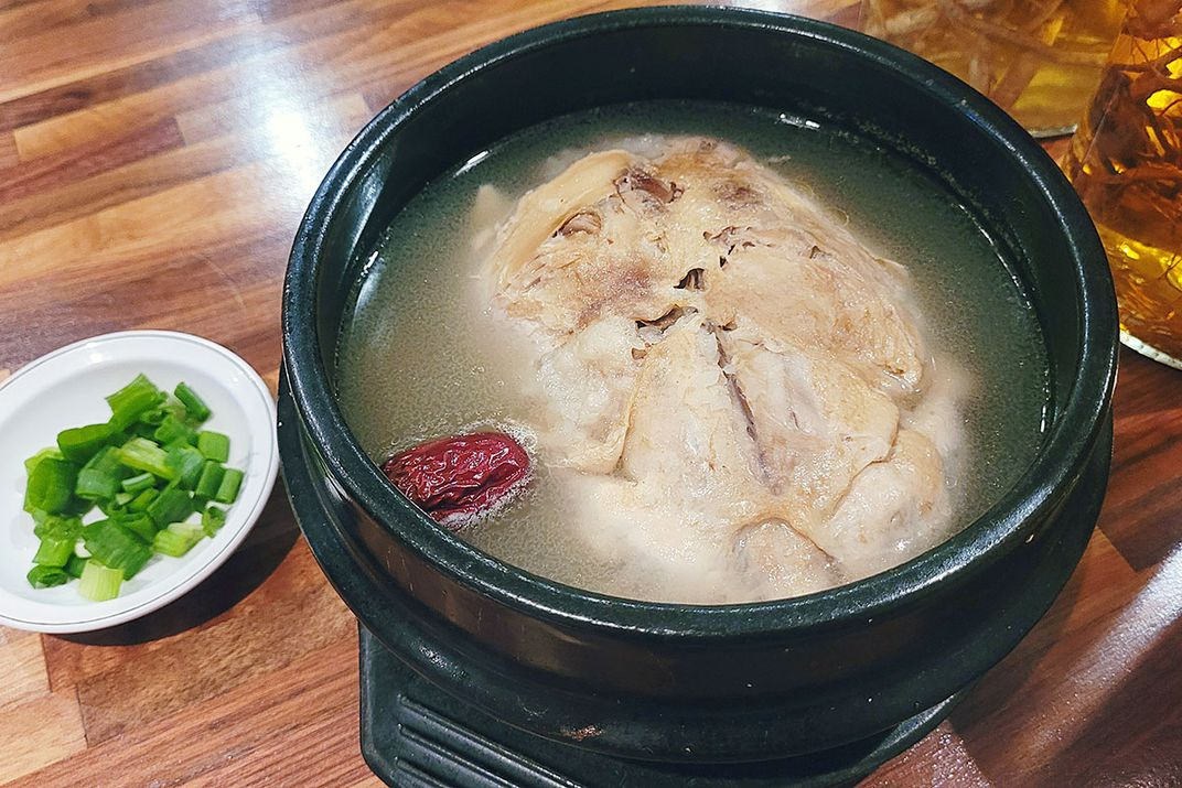 Closeup of a bowl of soup with a large piece of chicken, alongside a small dish of chopped green onion.