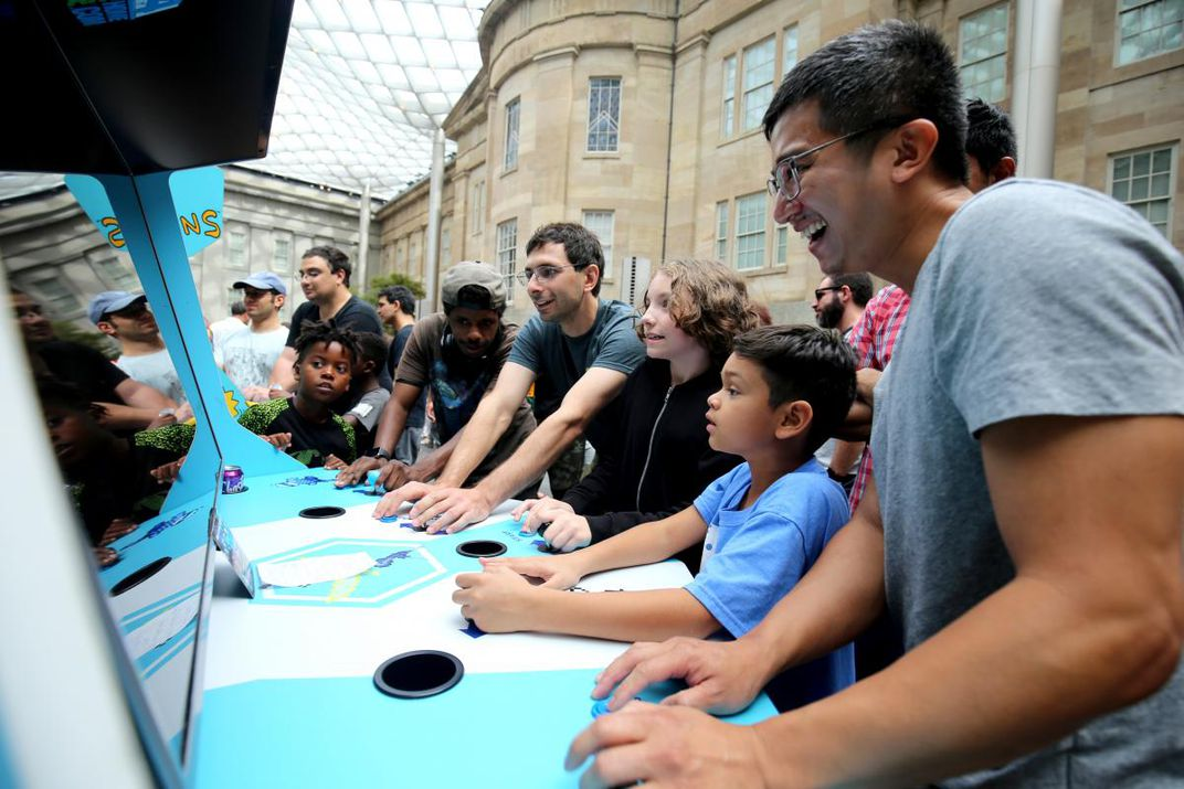 A photograph of six individuals playing a video game together.