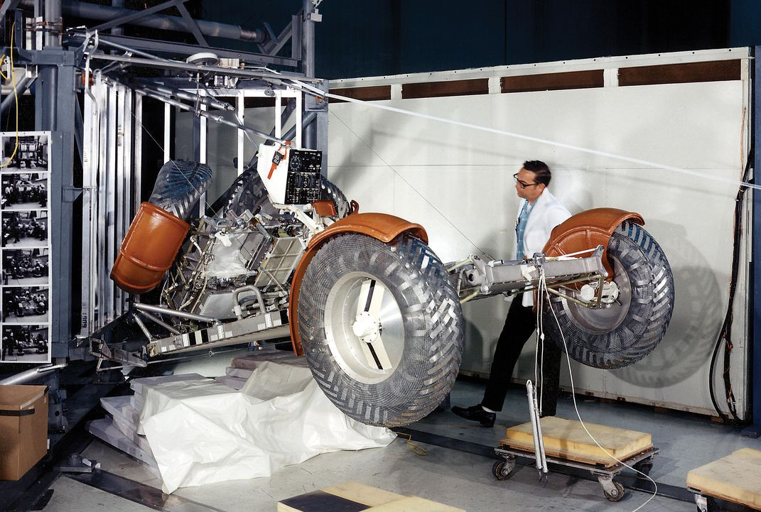 testing lunar rover deployment as man in white jacket inspects