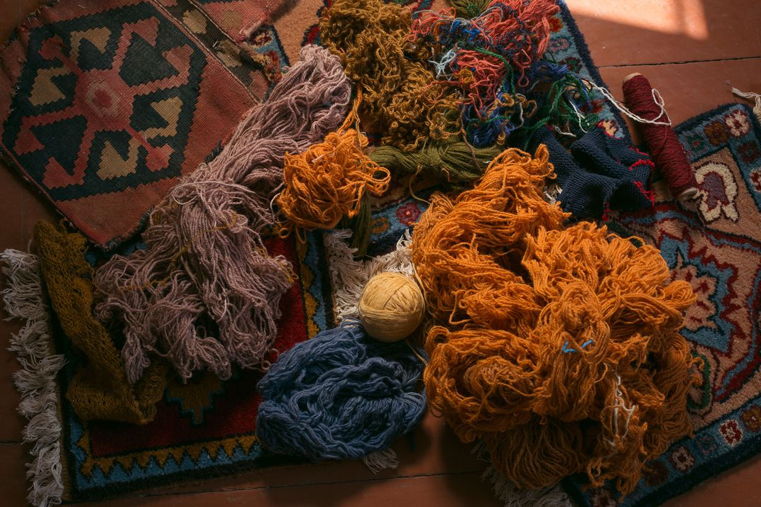 An arrangement of colorful yarn is placed carefully on top of a geometrically patterned rug.