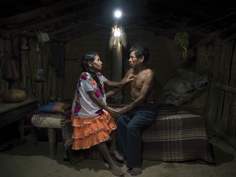 Faustina Flores Carranza (66) and her husband Juan Astudillo Jesus (63) sit in their solar-lit home in San Luis Acatlan, Guerrero, Mexico. Faustina and Juan have seven children and are together since 48 years. Like many members of the Mextica Indigenous Community, they have never had access to electricity. 