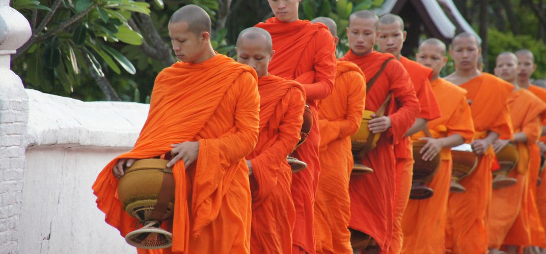Experience the rich tradition of Tak Bat while in Laos