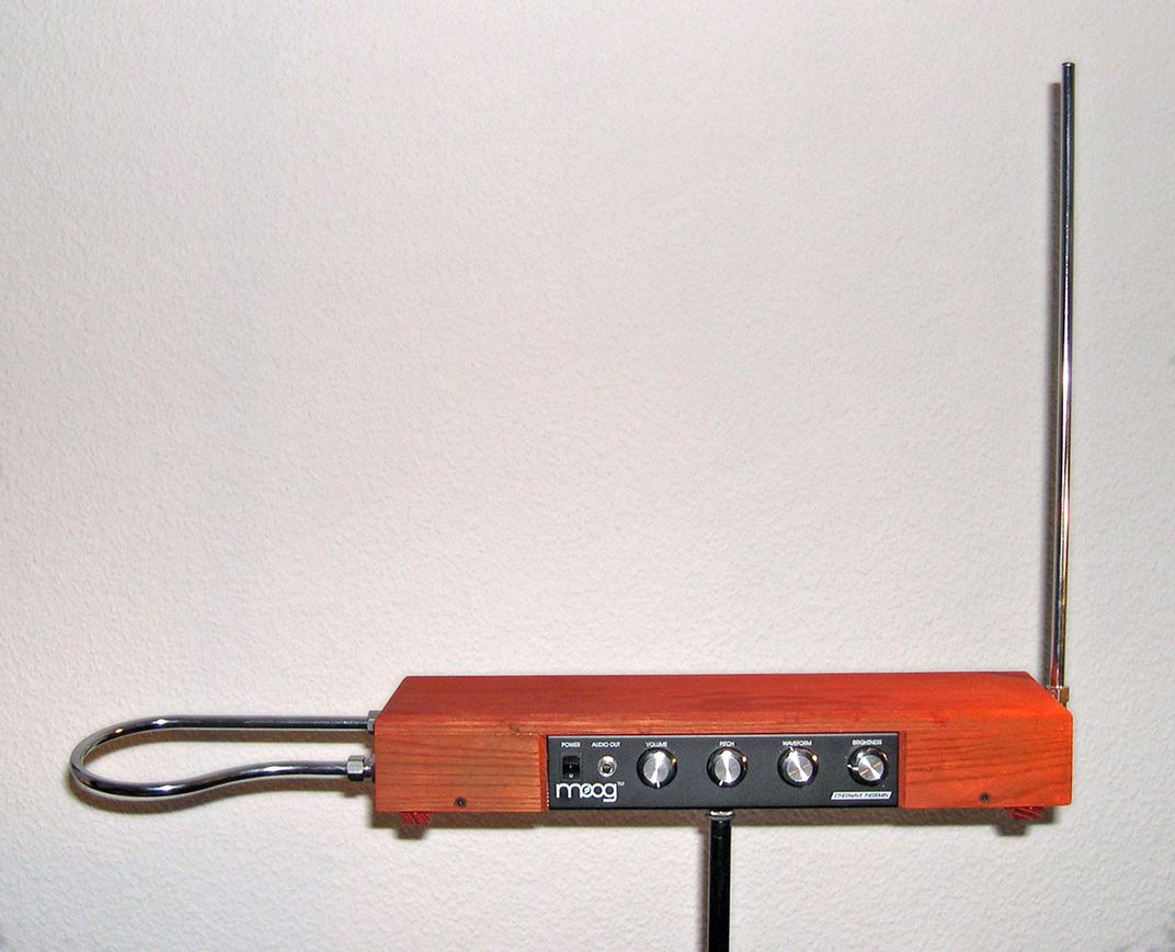 An orange box with buttons that resembles a radio, with a loop of metal jutting out its side (our left) and a long metal pole sticking up at a right angle on the other side, like a radio antenna (our right)
