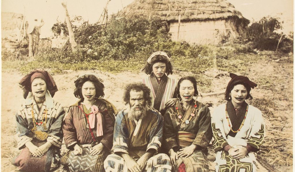 Ainu women and man outside a straw hut, from the Henry and Nancy Rosin Collection of Early Photography of Japan.