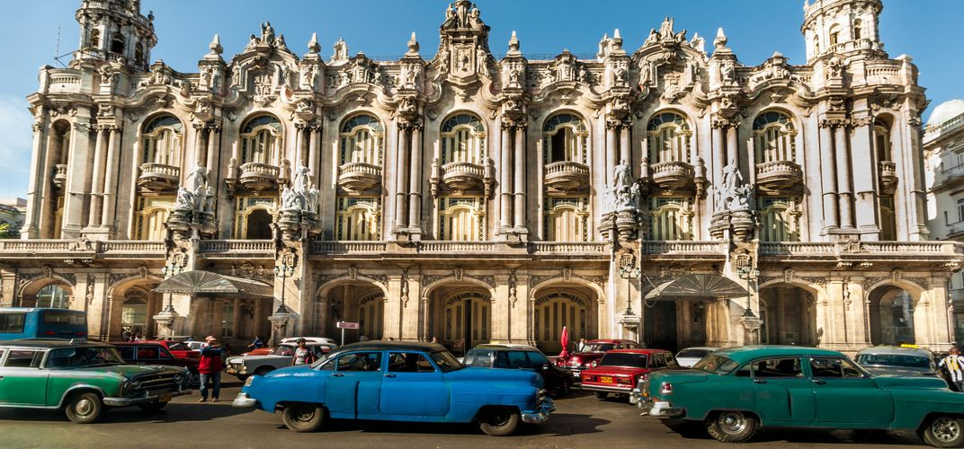 Historic building with vintage automobiles, Havana