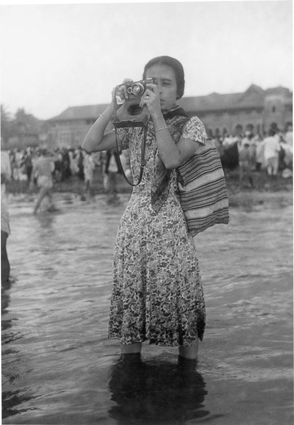 A black and white image of a woman in a dress standing ankle-deep in water, photographing something out of view of the camera