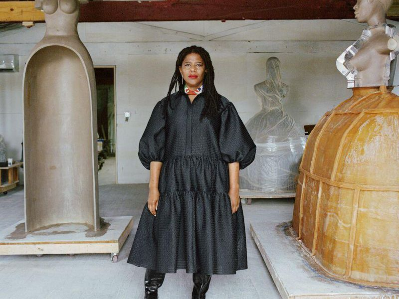 Simone Leigh, an African American woman, wears a voluminous black dress and stands in front of three of her sculptures, which are abstracted depictions of female figures on top of hoop skirts and jugs; Leigh faces the camera with a serious expression