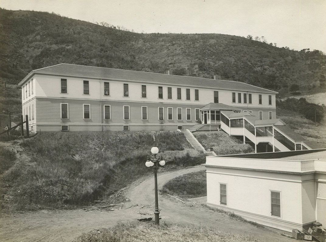 Long two-story building set on the side of a hill. Black-and-white archival photo.