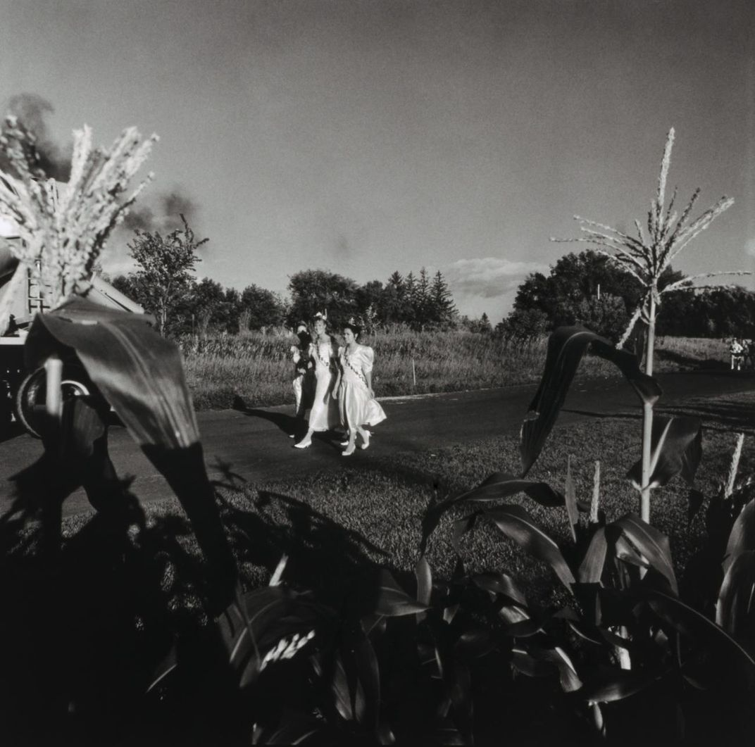 A photograph of three figures walking down a street.