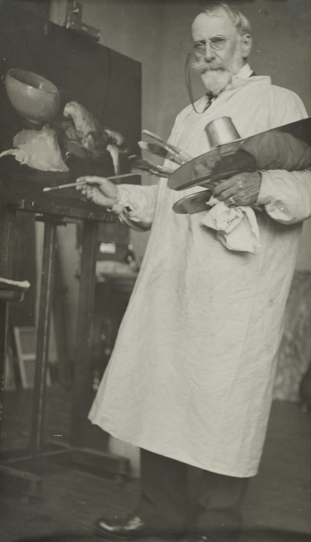 Photograph of William Merritt Chase painting in his studio.