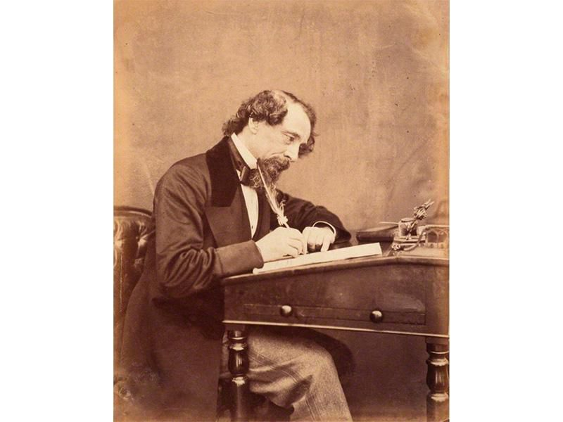 Charles Dickens, seen at his desk in 1858