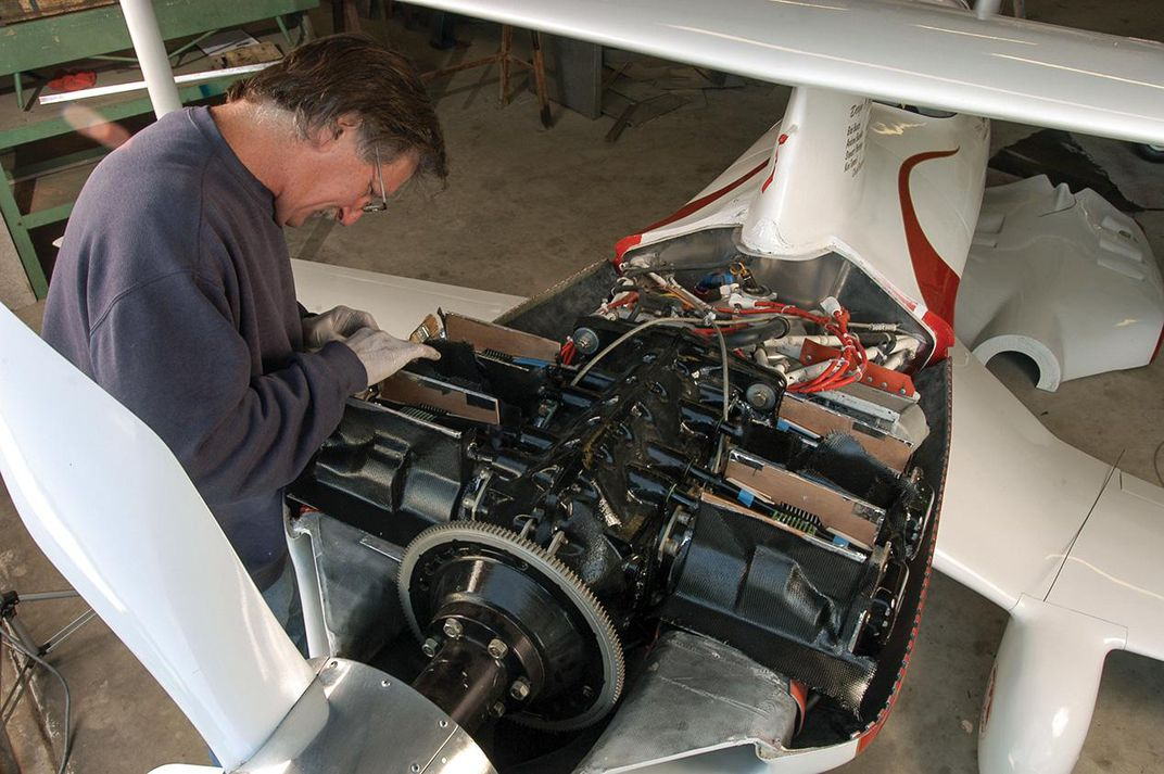Andy Paterson works on air-cooling of biplane