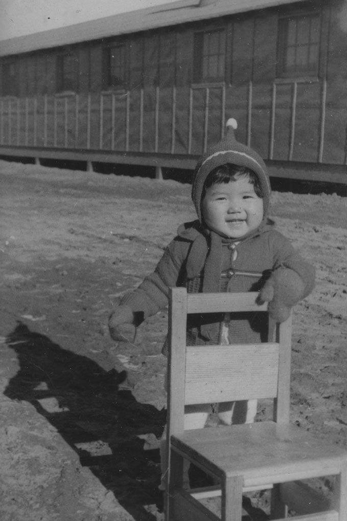 A black and white photo shows a small child smiling and holding a chair in front of a chainlink fence.