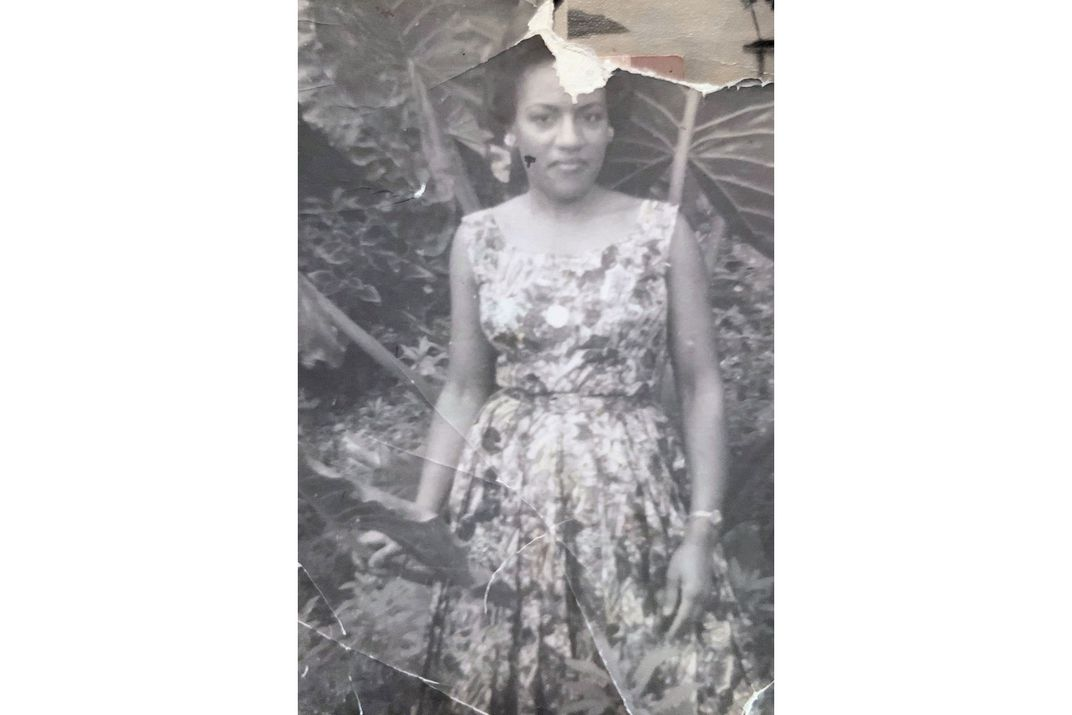 A woman posing among the wide leaves of a tropical plant, wearing a floral print dress. Black-and-white photo that is crumpled and torn.