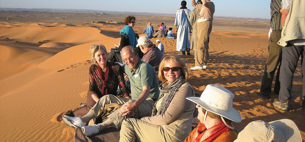 Smithsonian travelers relax on the sand dunes. Credit: Amy Kotkin