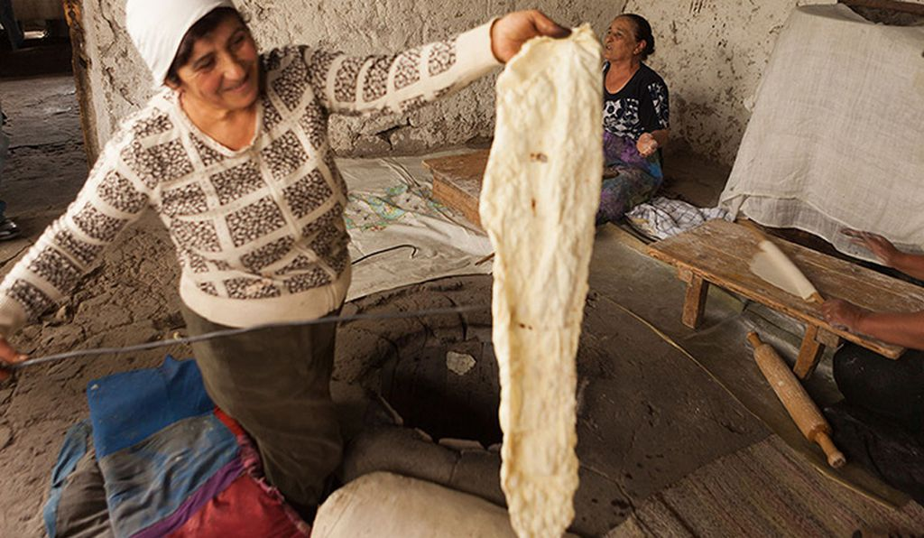 Arev Yenokyan displays the fruits of her labor: freshly baked lavash hot from the tonir.