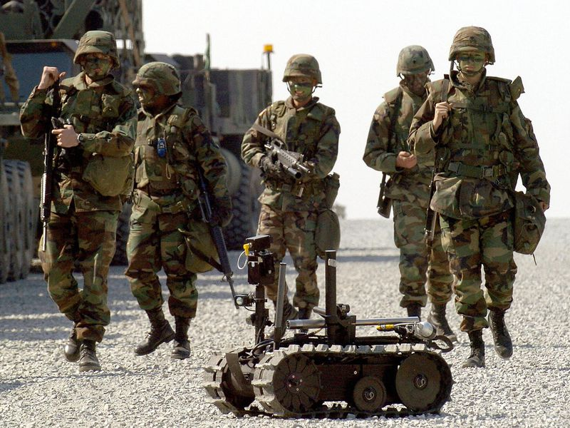 US soldiers walk behind a military robot during military exercises by US and South Korea troops