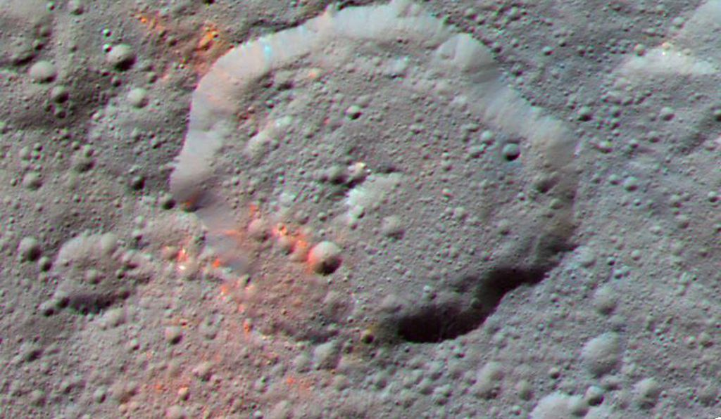 This image of a crater on Ceres shows bright red portions thought to contain organic material.