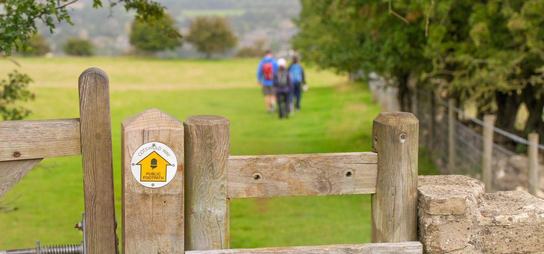 Signpost and ramblers on the Cotswolds Way