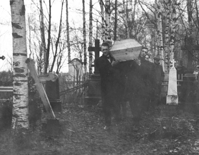 Men carry a casket among birch trees and tall cross headstones