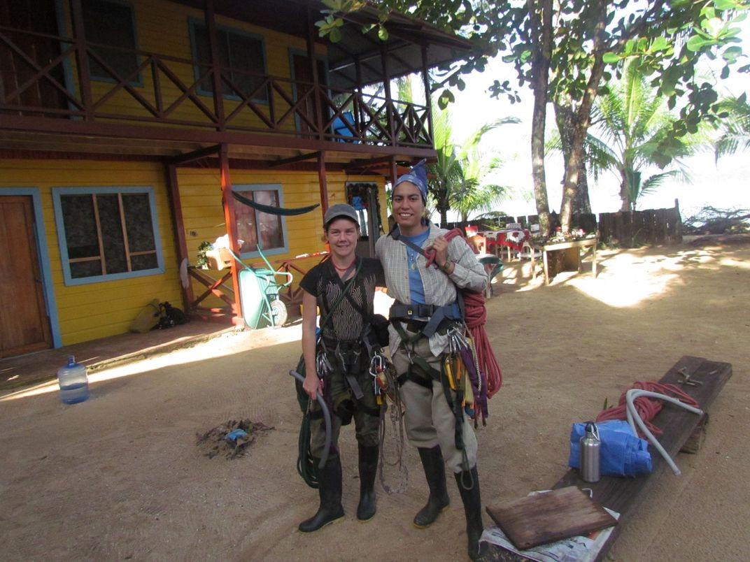 Conservation biologists Tremaine Gregory (left) and Farah Carrasco Rueda (right) pose for a photo in their climbing gear outside of a building in Panama during a tree-climbing course.