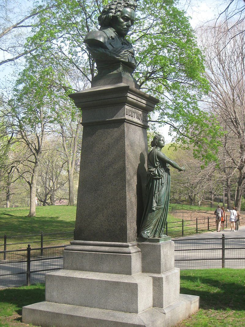 A pedestal surrounded by greenery in Central Park, with Beethoven's bust on top looking down and a smaller figure of a woman in robes standing beneath him