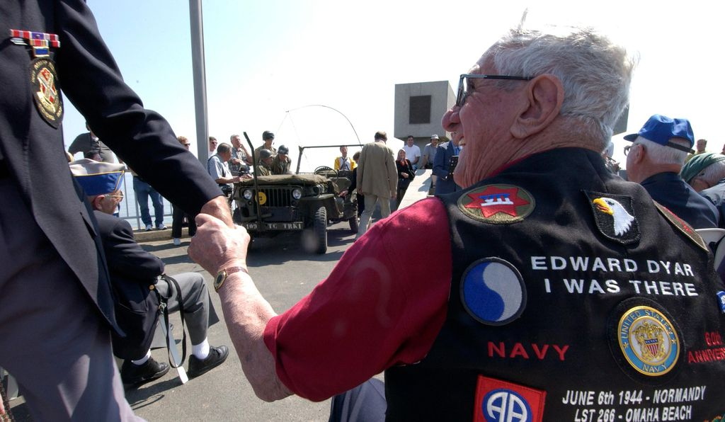 War veterans shake hands and exchange memories as they meet again for the 60th anniversary of D-Day, 2004.