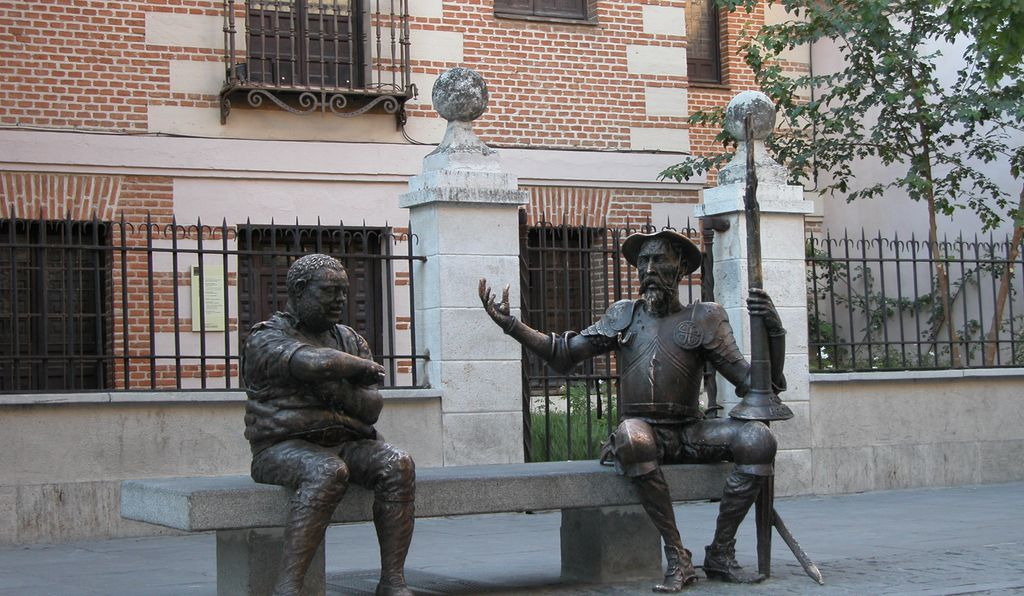 A bench outside Cervantes' Birthplace Museum, with Don Quixote and Sancho Panza.