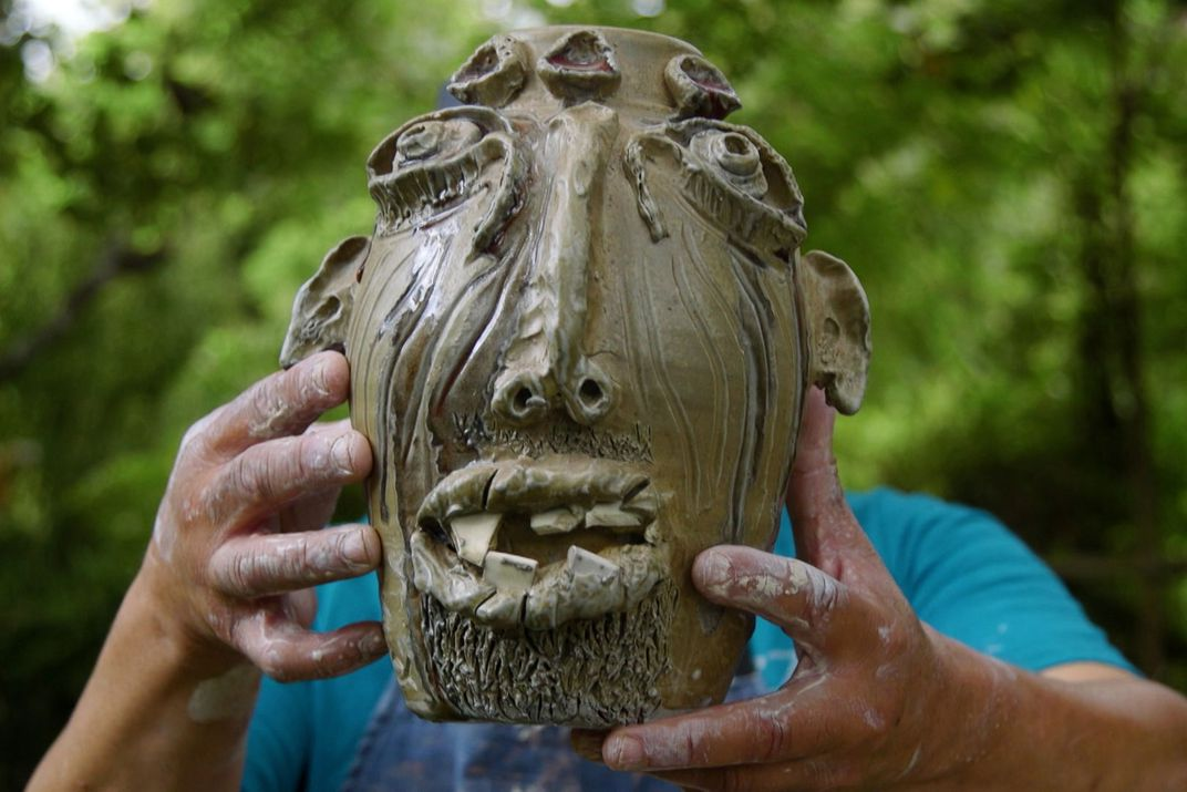 A man holds up a face jug, blocking his own face.