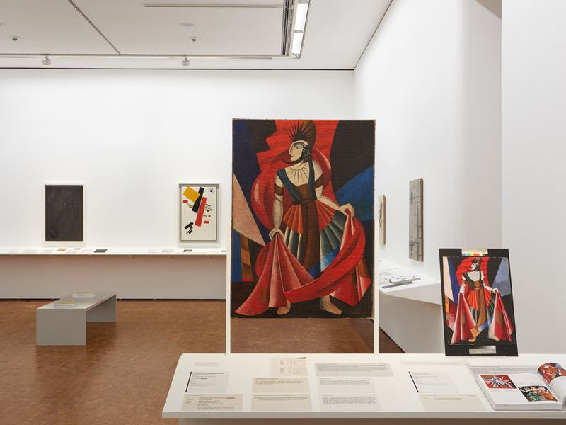 Stark white museum walls with canvases hanging on the walls at intervals; in foreground, a large red and black abstracted composition of a woman in a dress; to the right, a smaller version of the same work