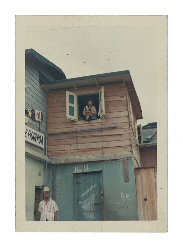 Photograph of a wooden house painted blue with red shutters. A woman leans out of an upstairs window holding a dog and a man is below on the street smoking a cigarette.