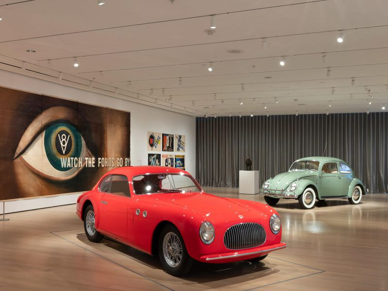 A view of a museum gallery with a bright red car on display in front of a light green Beetle; on the wall, an enormous lithograph of a human eye with the words Watch the Fords Go By