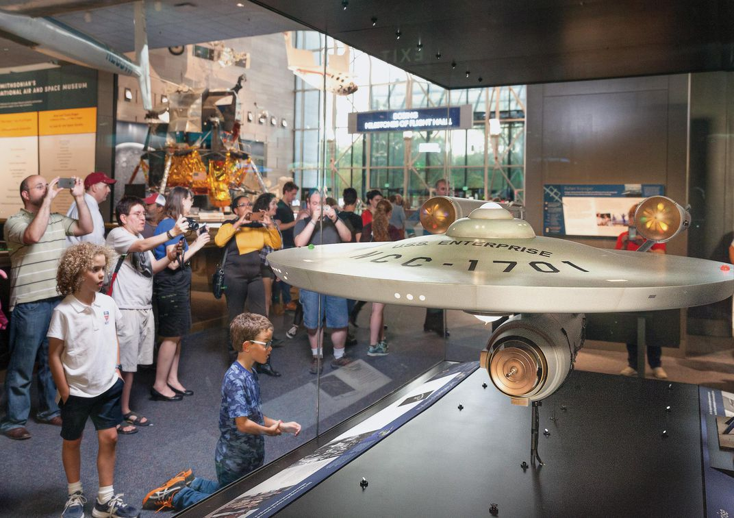museumgoers look at studio model of Enterprise