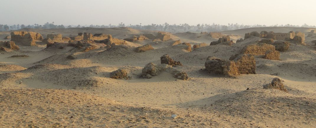 A panoramic view of sand and ruins of ancient brick structures