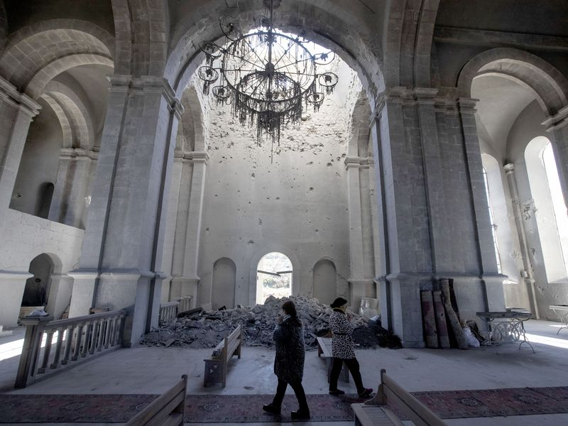 Two people walk, cast in shadows, underneath the tall white arches of a cathedral; behind them, a pile of rubble blocks a doorway and a broken chandelier hangs from the ceiling