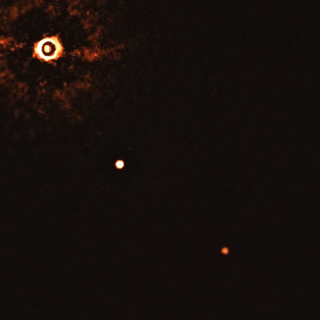 On the far left, a bright object that radiates light (the star); a bright white light near the center of the image is the larger exoplanet and a further, dimmer orange pinprick is the smaller planet