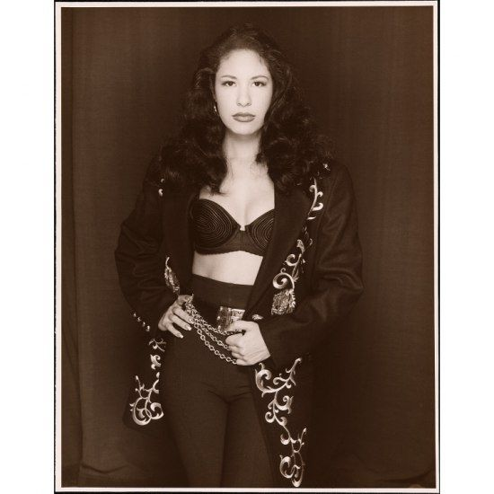 Black and white photo of Selena in black pants and embroidered jacket