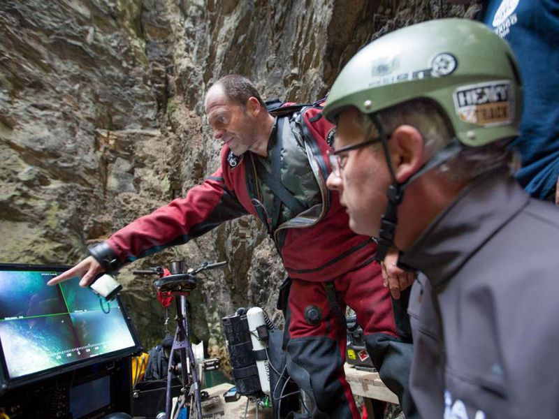 Polish explorers check a footage from a remote-operated vehicle deep in the Czech Republic's deepest cave.