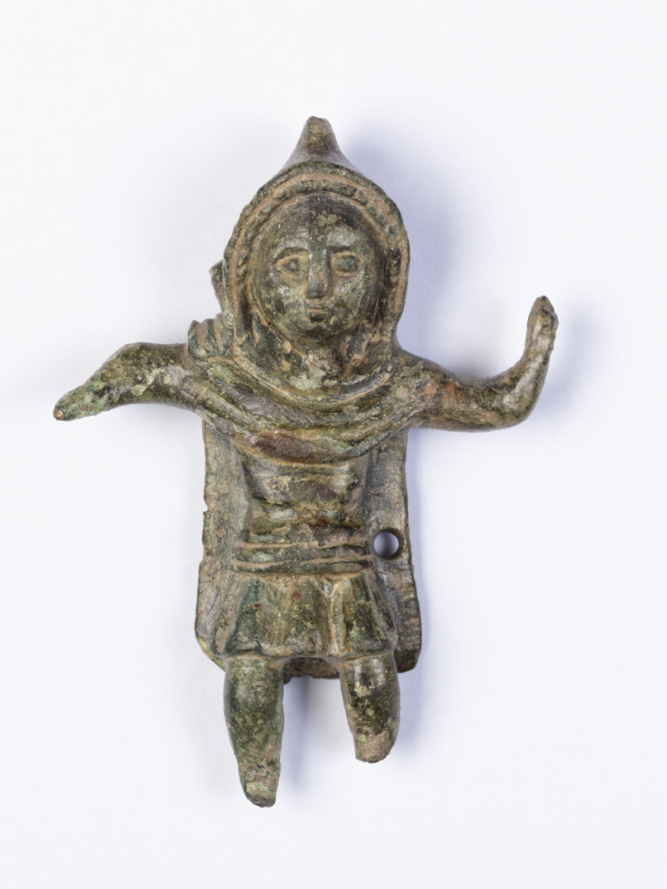 Against a white background, a small figurine with one arm raised and the other extended, wearing a hooded cloak