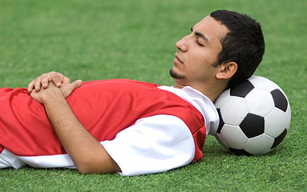 a footballer resting his head on football