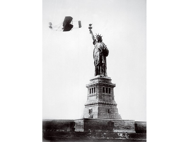 Wright plane passing Statue of Liberty