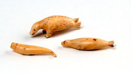 ivory figurines of a seal walrus and beluga whale.