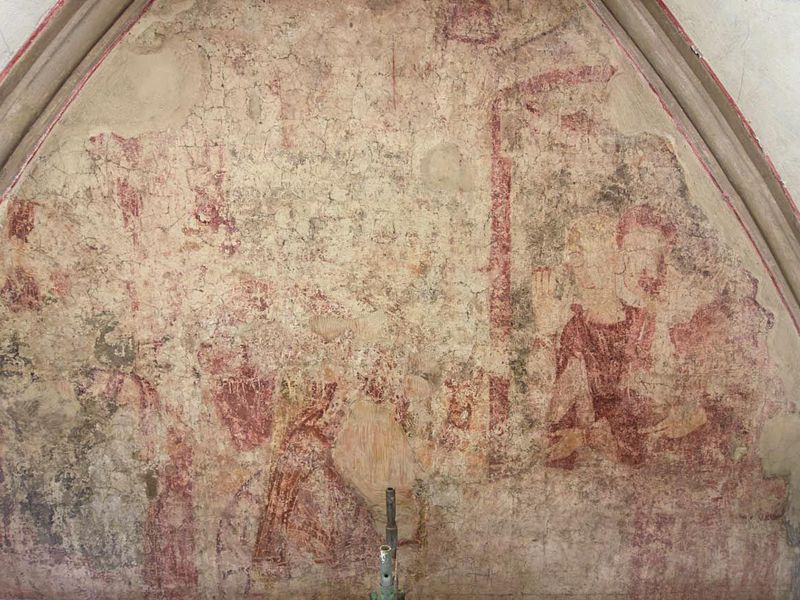 A very faded red and taupe frescoe with the outlines of some figures visible, enclosed in an arched dome