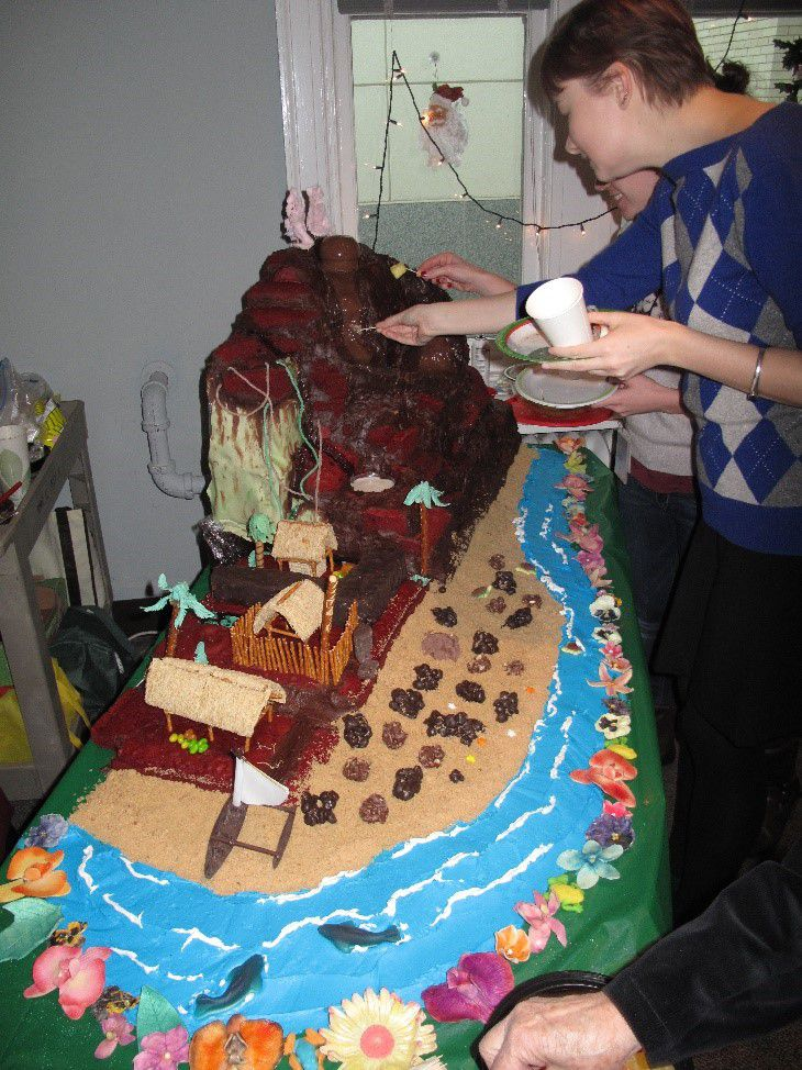 Brown volcano made of cake surrounded by an edible blue river and beige sand modeled after a volcano in Hawaii.