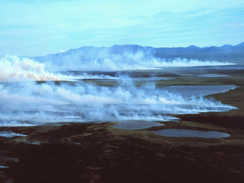 A photograph of a tundra landscape with mountains on the horizon and smoke rising from the ground