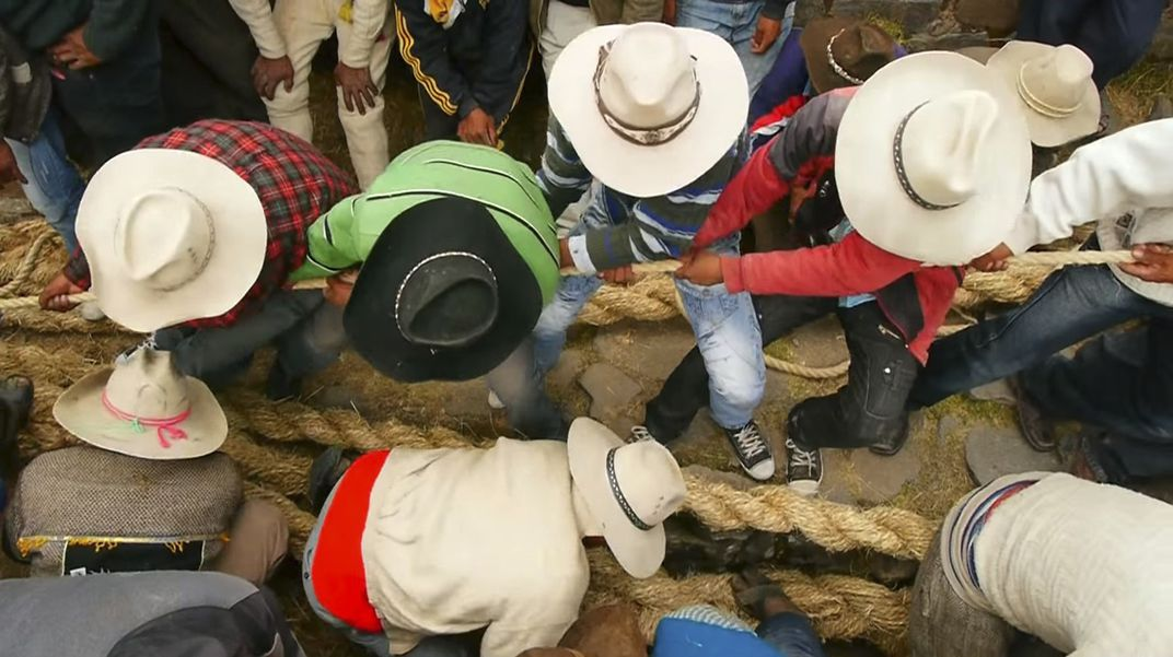 Men bend over to pull very large woven-grass cables taut. The perspective is from above, so what is seen is the crowns of the men's cowboy hats, their grip on the thick cables, and their position back on their heels as they pull.