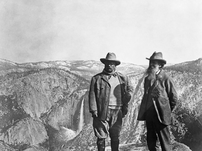 Theodore Roosevelt stands with naturalist John Muir on Glacier Point, above Yosemite Valley, California, USA.