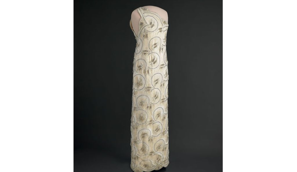 Nancy Reagan's 1981 Inaugural Gown at the National Museum of American History. The dress is a beaded, one-shouldered white sheath gown of lace over silk satin, designed by James Galanos.