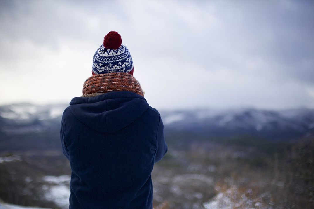 A person wearing a knit hat and scarf standing on a cliff.